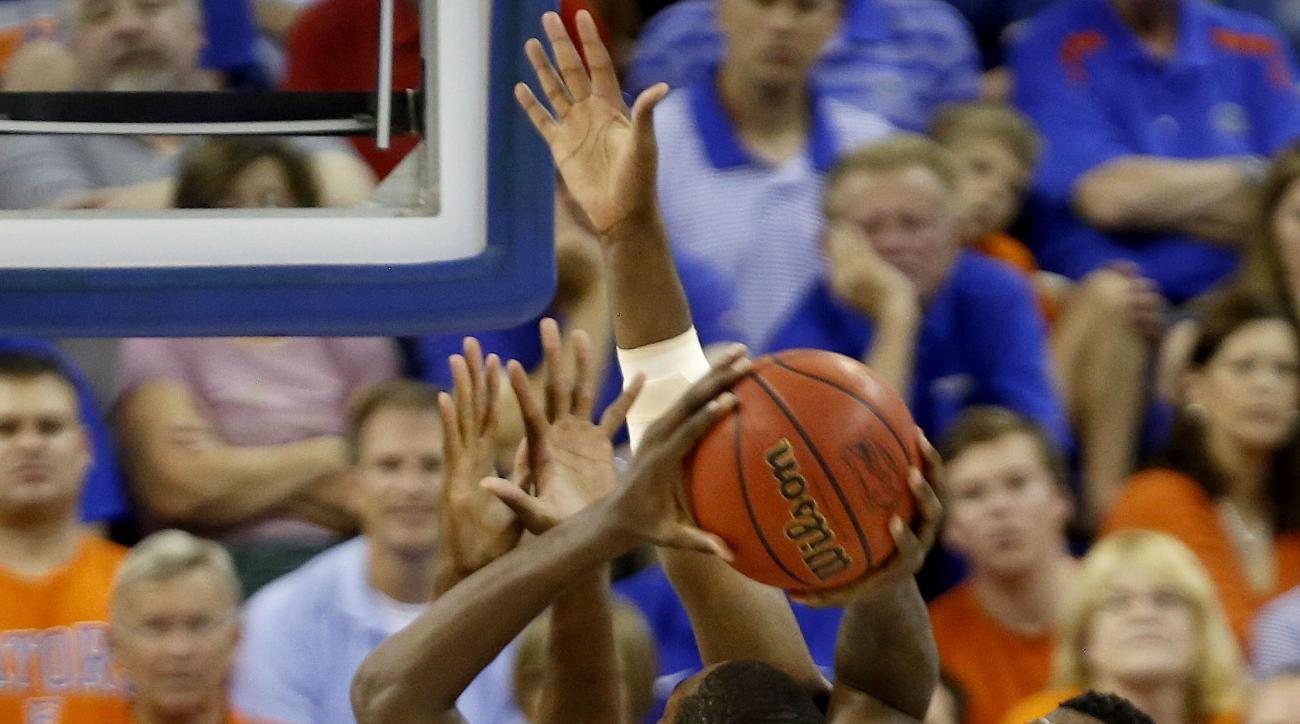 Florida forward Dorian Finney-Smith (10) is called for a charge while taking a shot as he is  defended by Arkansas center Willy Kouassi (50) and forward Trey Thompson (1) during the first half of an NCAA college basketball game at the O'Connell Center on