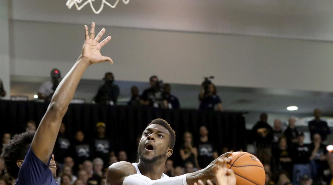 FILE - This Nov. 28, 2015 file photo, shows Virginia Commonwealth's JeQuan Lewis as he goes to the basket against Old Dominion's Ambrose Mosley, left, and Ahmad Caver, right, during the second half of an NCAA college basketball game in Richmond, Va. Lewis