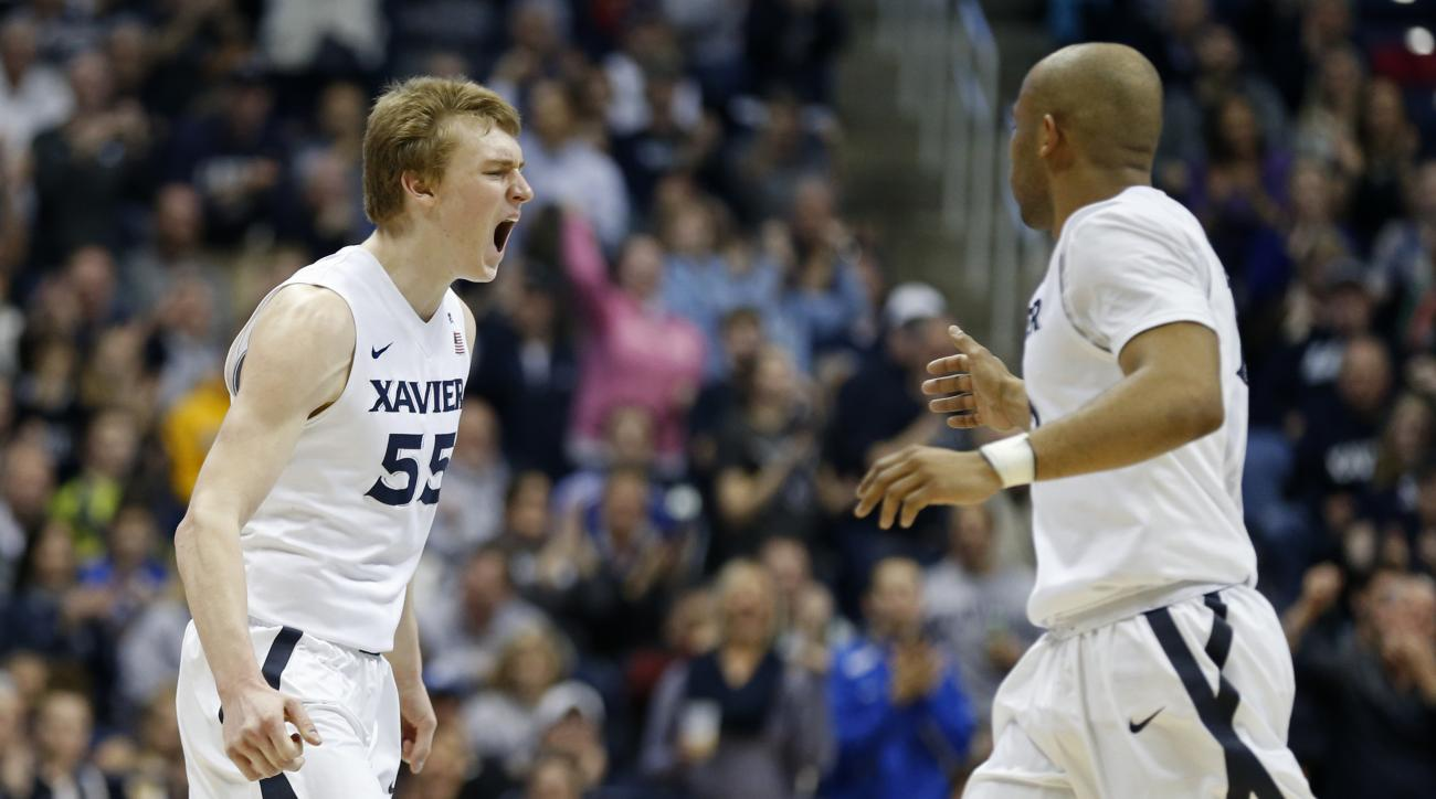 Xavier guard J.P. Macura (55) celebrates a 3-point basket against Marquette with Myles Davis, right, during the second half of an NCAA college basketball game Saturday, Feb. 6, 2016, in Cincinnati. Xavier won 90-82. (AP Photo/Gary Landers)