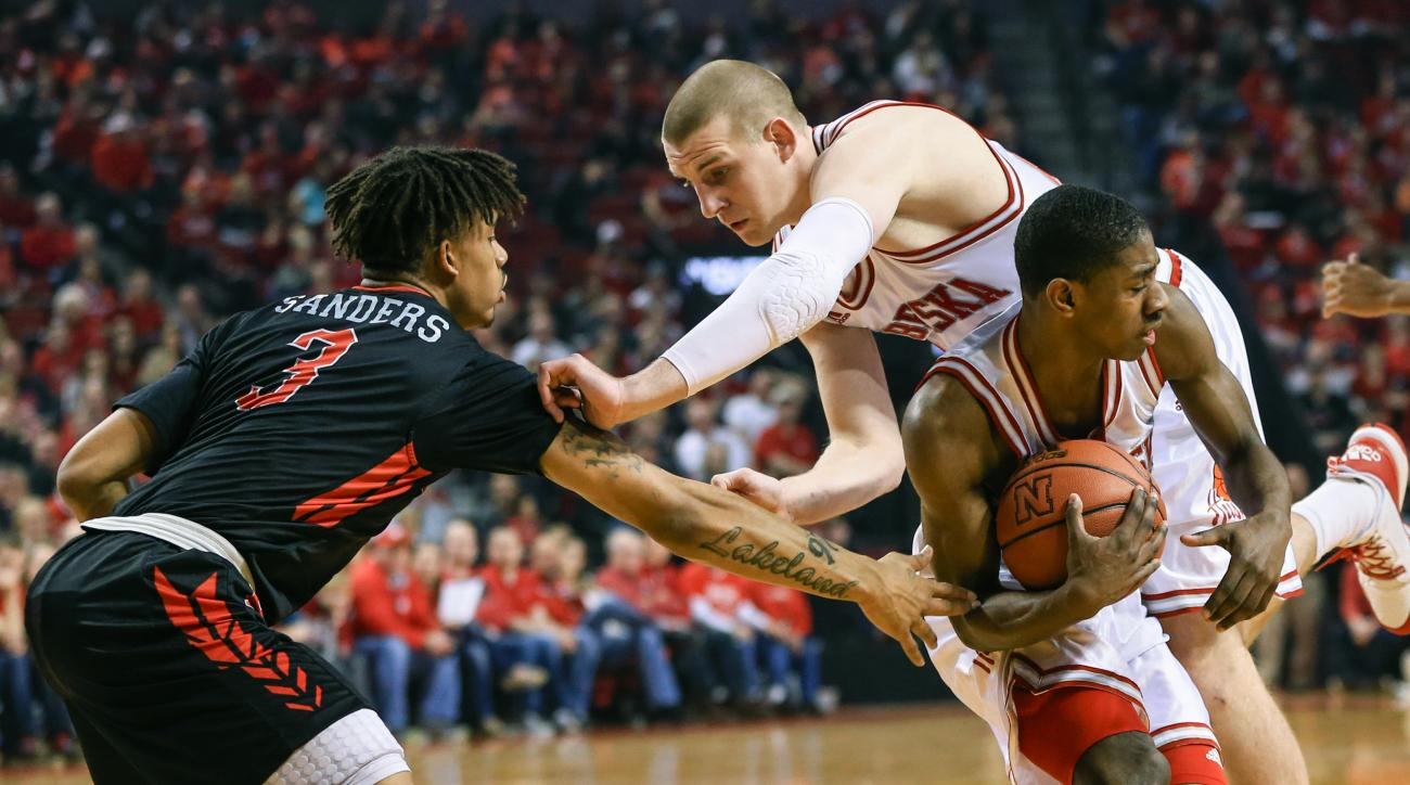 Nebraska's Nick Fuller, center, stumbles over Nebraska's Glynn Watson Jr., right, who is guarded by Rutgers' Corey Sanders (3) during the first half of an NCAA college basketball game in Lincoln, Neb., Saturday, Feb. 6, 2016. (AP Photo/Nati Harnik)