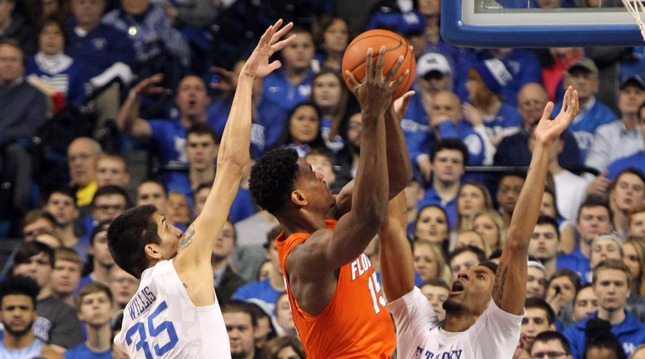 Florida's John Egbunu, center, shoots between Kentucky's Derek Willis (35) and Marcus Lee (00) during the first half of an NCAA college basketball game Saturday, Feb. 6, 2016, in Lexington, Ky. (AP Photo/James Crisp)