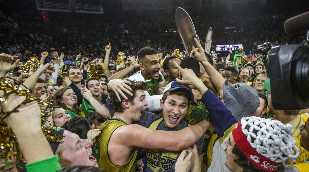 Notre Dame's Steve Vasturia (32), center left, celebrates on the court with fans following his team's 80-76 win against North Carolina in an NCAA college basketball game Saturday, Feb. 6, 2016, in South Bend, Ind. (AP Photo/Robert Franklin)