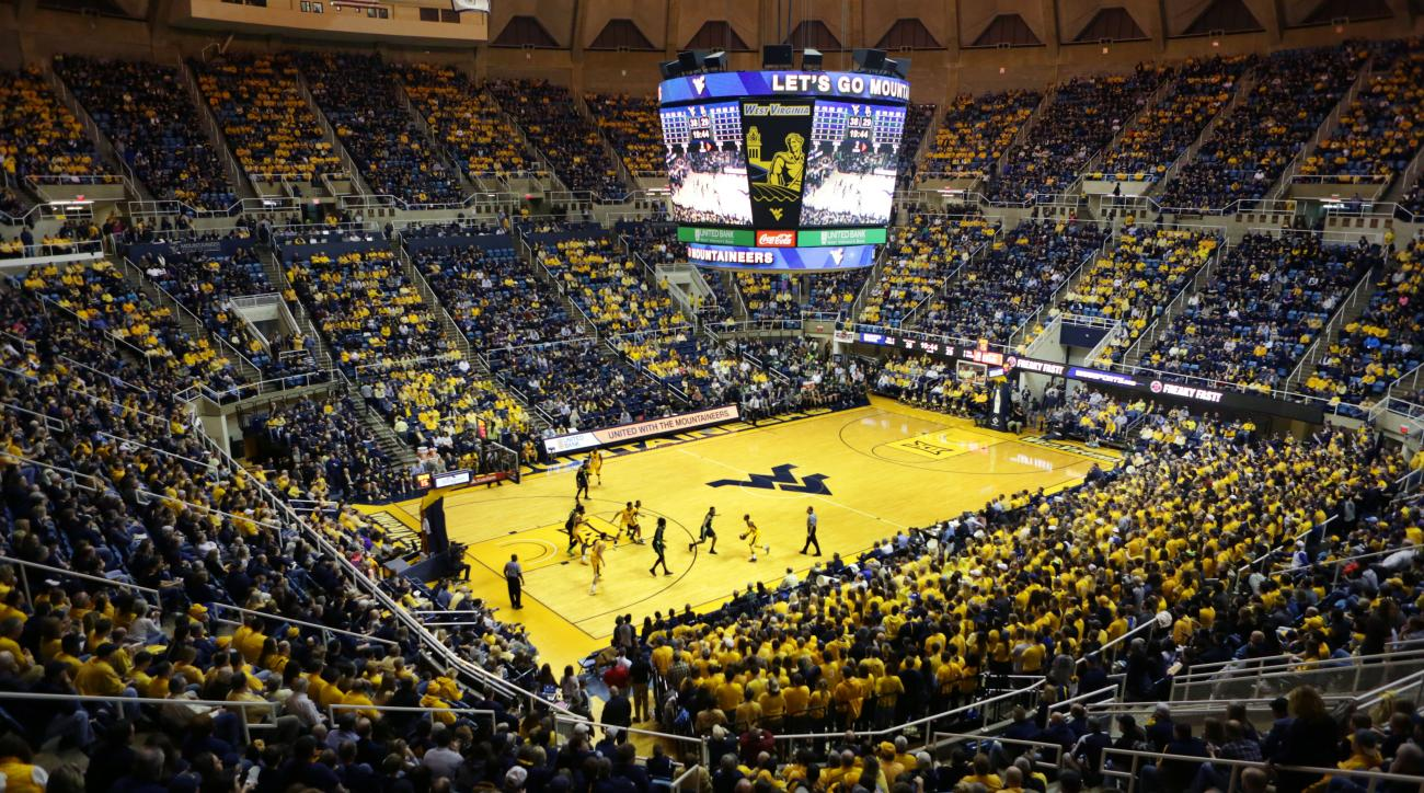 West Virginia fans wear yellow during the second half of an NCAA college basketball game against Baylor, Saturday, Feb, 6, 2016, in Morgantown, W.Va. (AP Photo/Raymond Thompson)