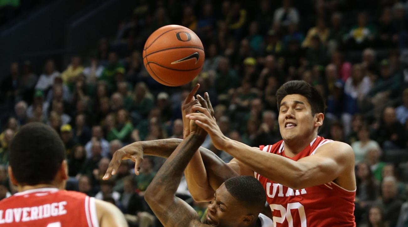 As Utah's Jordan Loveridge looks on, left, Oregon's Elgin Cook is fouled by Utah's Chris Reyes during a rebound attempt during the first half of an NCAA college basketball game Sunday, Feb. 7, 2016 in Eugene, Ore. (AP Photo/Chris Pietsch)