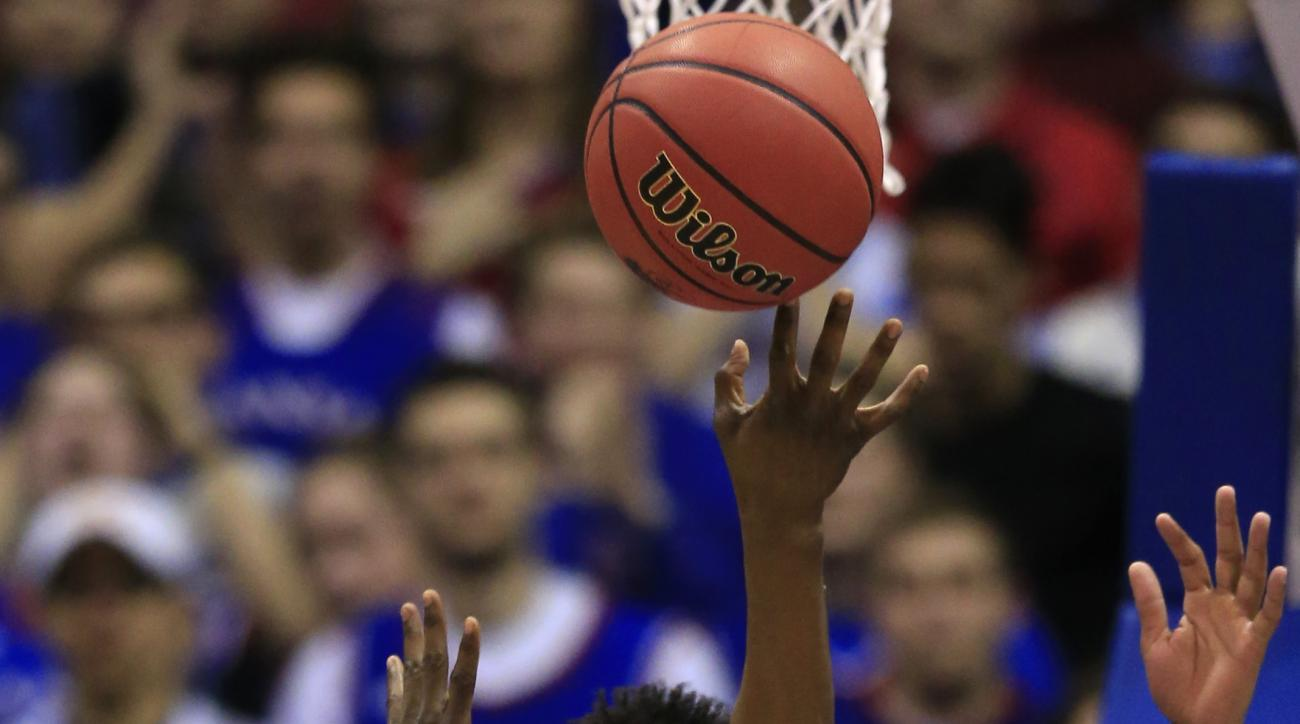 West Virginia guard Teyvon Myers (0) shoots over Kansas guard Devonte' Graham (4) during the first half of an NCAA college basketball game in Lawrence, Kan., Tuesday, Feb. 9, 2016. (AP Photo/Orlin Wagner)