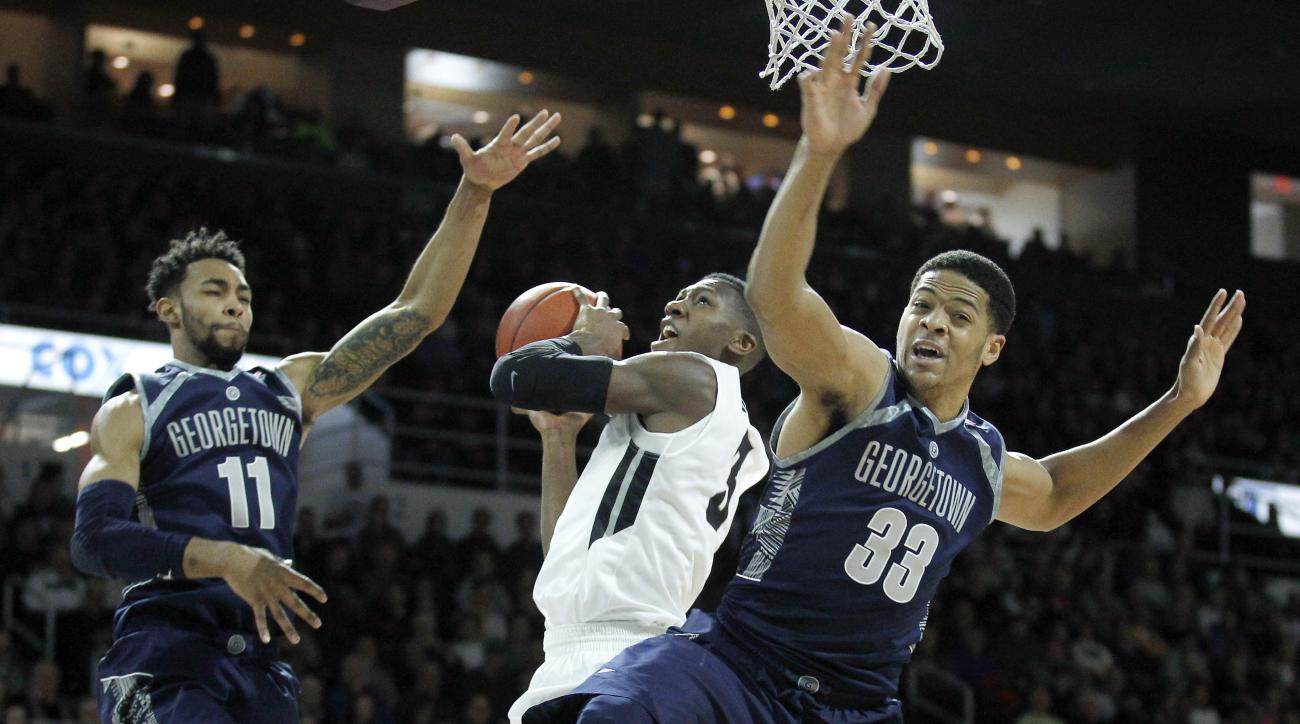 Providence guard Kris Dunn (3) shoots the ball as Georgetown forward Isaac Copeland (11) and forward Trey Mourning (33) defend during the first half of an NCAA college basketball game in Providence, R.I., Saturday, Feb. 13, 2016. (AP Photo/Stew Milne)