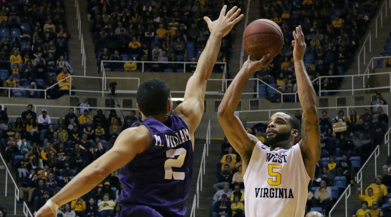 West Virginia guard Jaysean Paige (5) takes a shot over TCU guard Michael Williams (2) during the second half of an NCAA college basketball game, Saturday, Feb, 13, 2016, in Morgantown, W.Va. (AP Photo/Raymond Thompson)