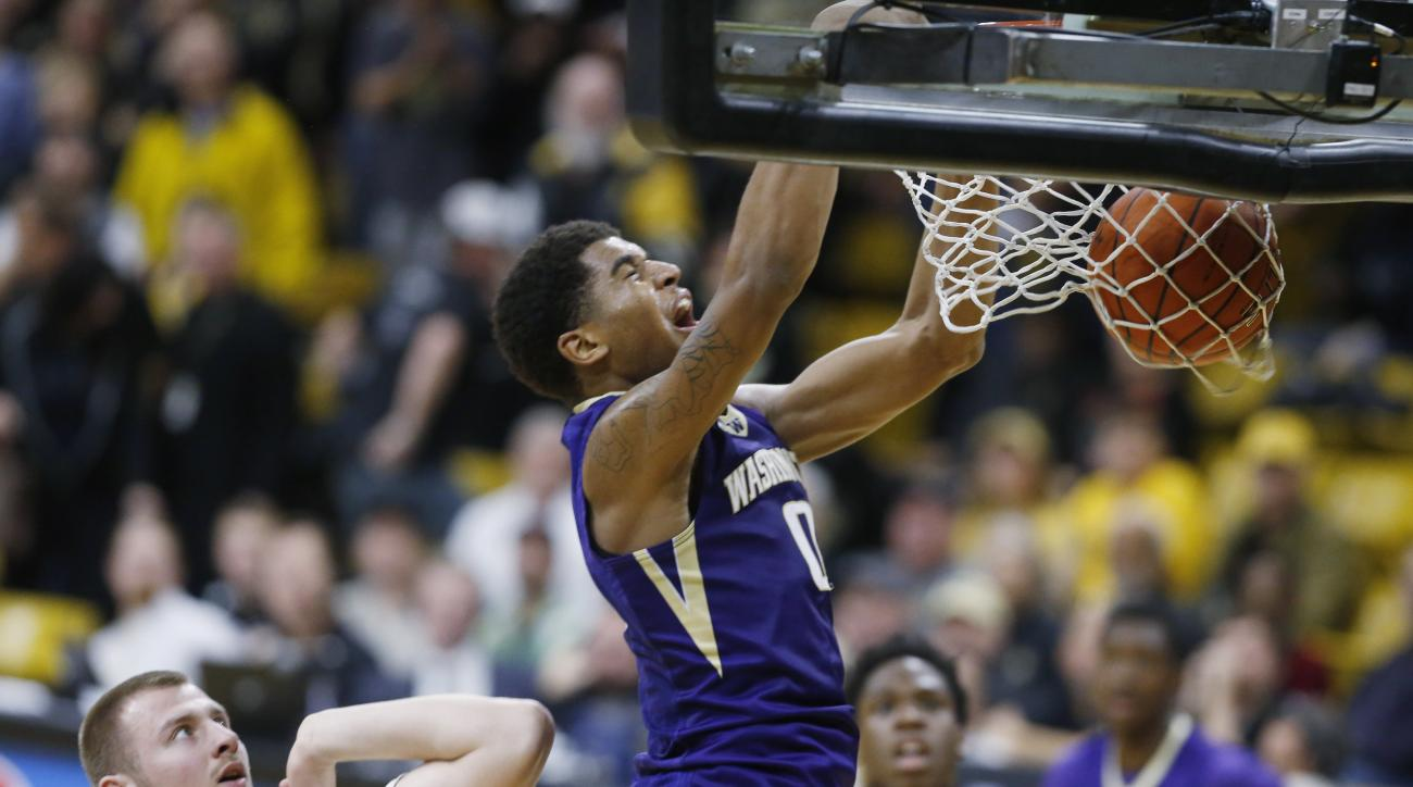 Washington forward Marquese Chriss, right, reacts as he dunks the ball for a basket over Colorado forward Kenan Guzonjic in the first half of an NCAA college basketball game Saturday, Feb. 13, 2016, in Boulder, Colo. (AP Photo/David Zalubowski)