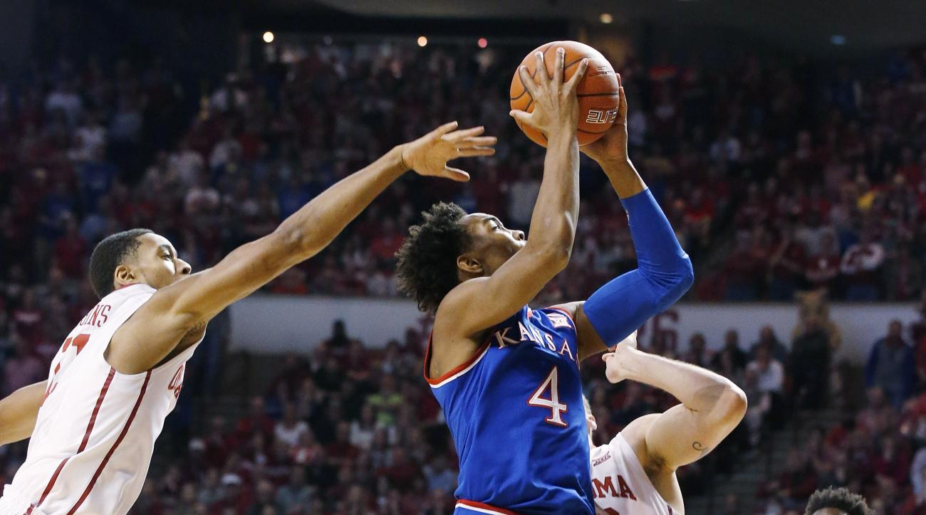 Kansas guard Devonte' Graham (4) shoots between Oklahoma guard Isaiah Cousins, left, forward Ryan Spangler, center, and forward Khadeem Lattin, right, in the first half of an NCAA college basketball game in Norman, Okla., Saturday, Feb. 13, 2016. (AP Phot