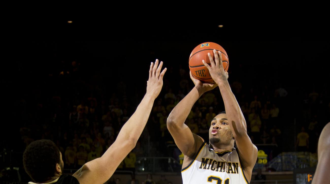 Purdue guard Kendall Stephens (21) defends a shot attempt from Michigan guard Zak Irvin (21) in the second half of an NCAA college basketball game at Crisler Center in Ann Arbor, Mich., Saturday, Feb. 13, 2016. Michigan won 61-56. (AP Photo/Tony Ding)