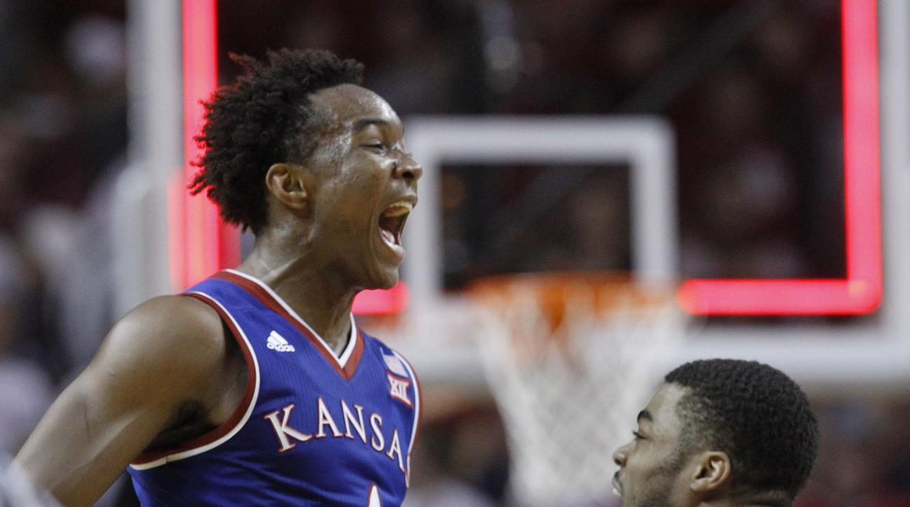 Kansas guard Devonte' Graham (4) celebrates with teammate Frank Mason III, right, at the end an NCAA college basketball game against Oklahoma in Norman, Okla., Saturday, Feb. 13, 2016. Kansas won 76-72. (AP Photo/Sue Ogrocki)
