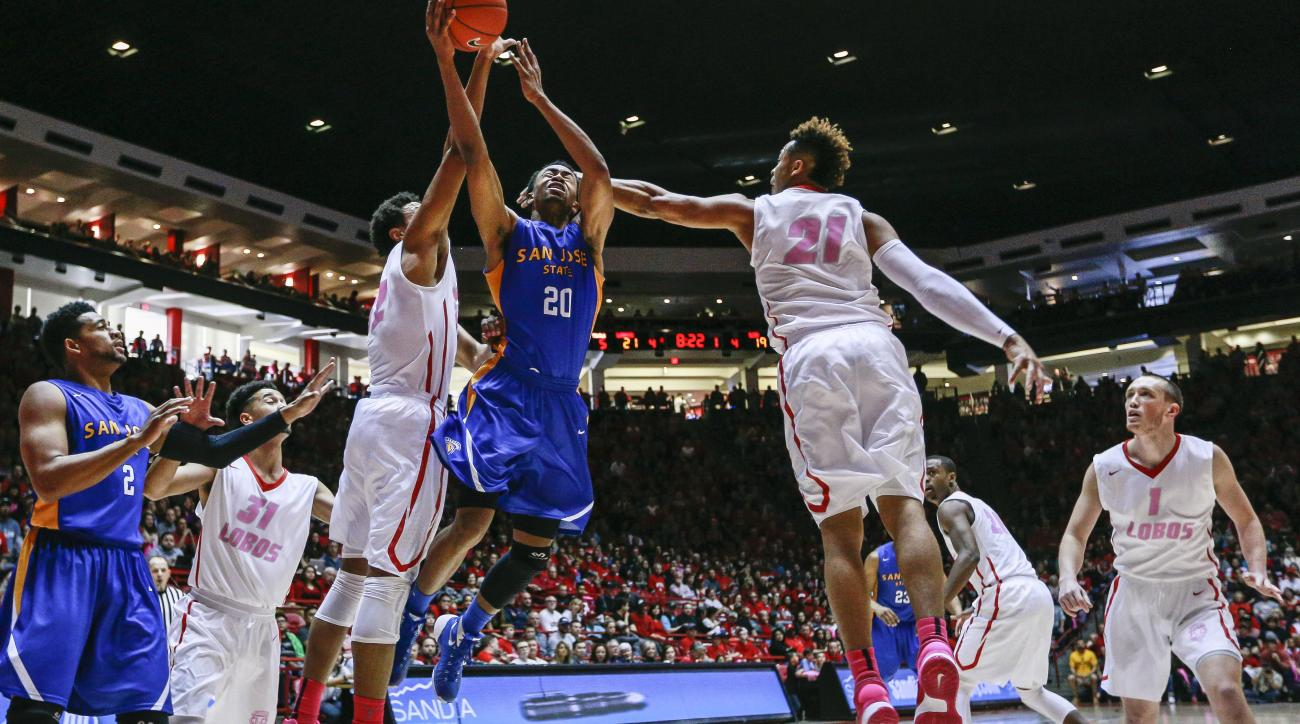 San Jose State's Isaac Thornton (20) drives between New Mexico's Tim Williams, left center, and Xavier Adams (21) during the first half of an NCAA college basketball game Saturday, Feb. 13, 2016, in Albuquerque, N.M. (AP Photo/Juan Labreche)