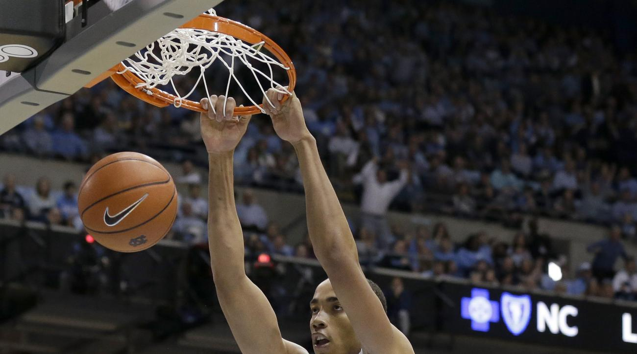 North Carolina's Brice Johnson (11) dunks as Pittsburgh's Cameron Johnson (23) looks on during the first half of an NCAA college basketball game in Chapel Hill, N.C., Sunday, Feb. 14, 2016. (AP Photo/Gerry Broome)