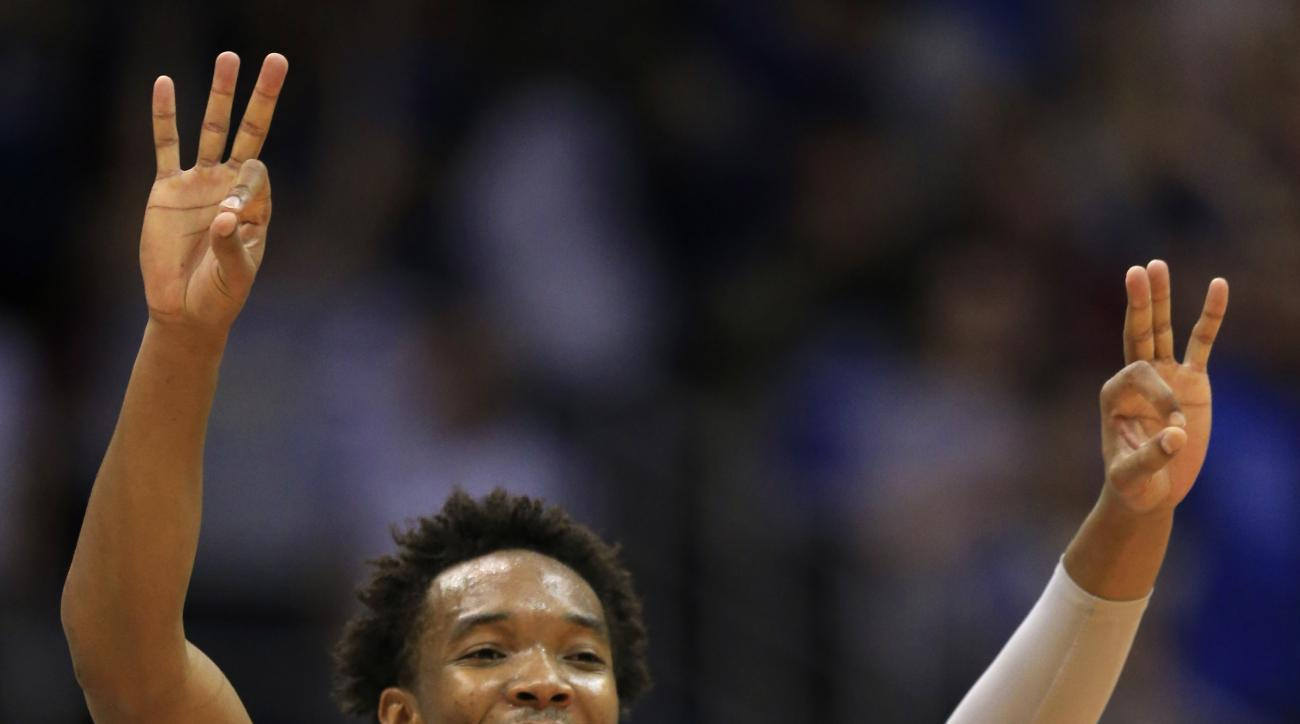 Kansas guard Devonte' Graham (4) celebrates a three-point basket during the first half of an NCAA college basketball game against Oklahoma State in Lawrence, Kan., Monday, Feb. 15, 2016. (AP Photo/Orlin Wagner)