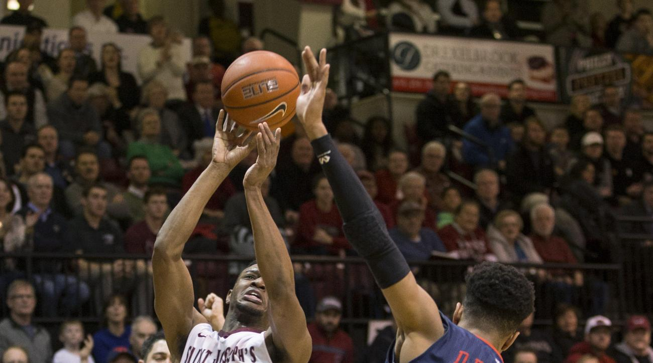 Saint Joseph's James Demery (25) tries to put up the shot as he is fouled by Dayton's Darrell Davis (1) during the first half of an NCAA college basketball game Wednesday, Feb. 17, 2016, in Philadelphia. (AP Photo/Chris Szagola)