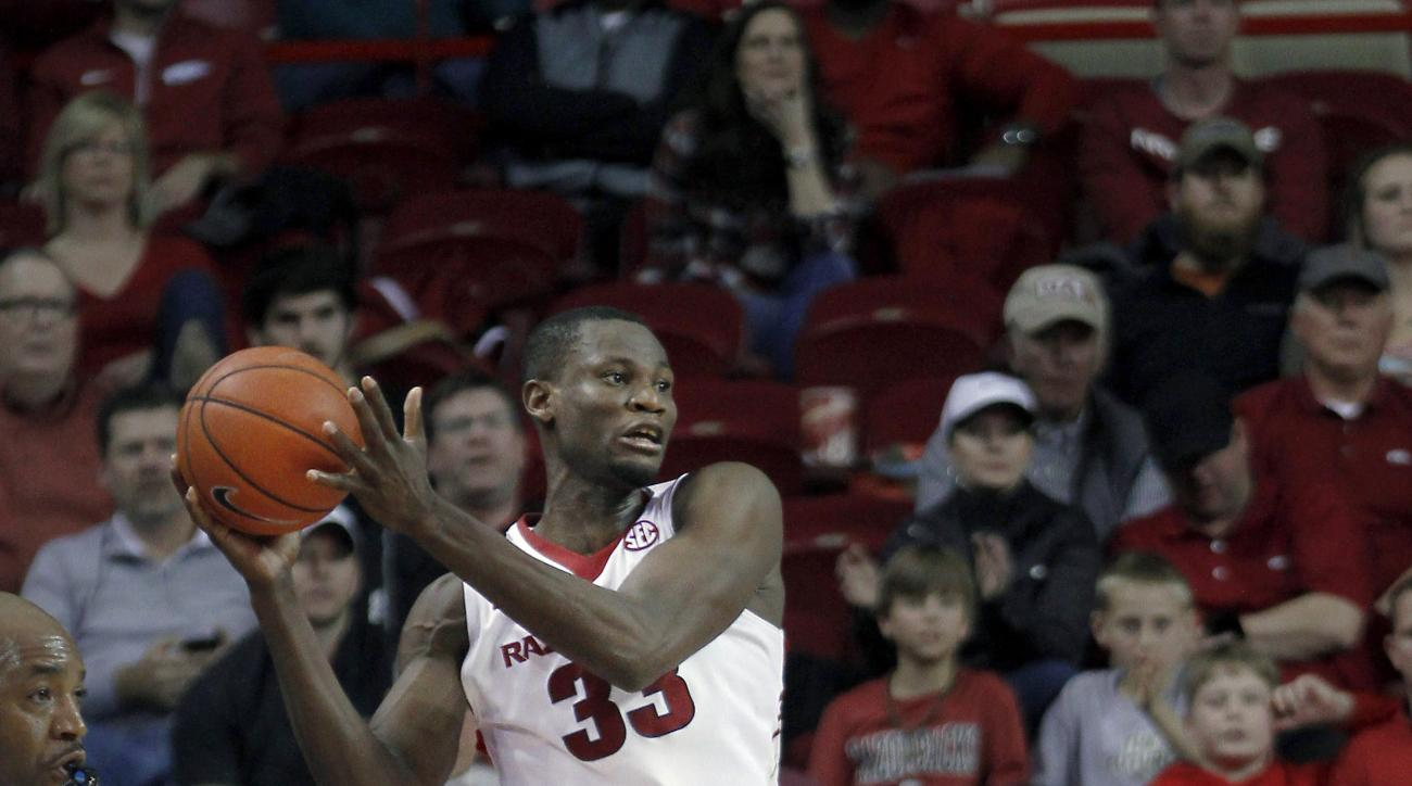 Arkansas' Moses Kingsley (33) saves the ball from going out of bounds during the second half of an NCAA college basketball game against Auburn, Wednesday, Feb. 17, 2016, in Fayetteville, Ark. Auburn beat Arkansas 90-86. (AP Photo/Samantha Baker)