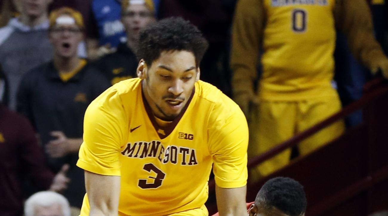 Maryland's Robert Carter, right, falls as he tries to get to the ball along with Minnesota's Jordan Murphy during the first half of an NCAA college basketball game Thursday, Feb. 18, 2016, in Minneapolis. (AP Photo/Jim Mone)