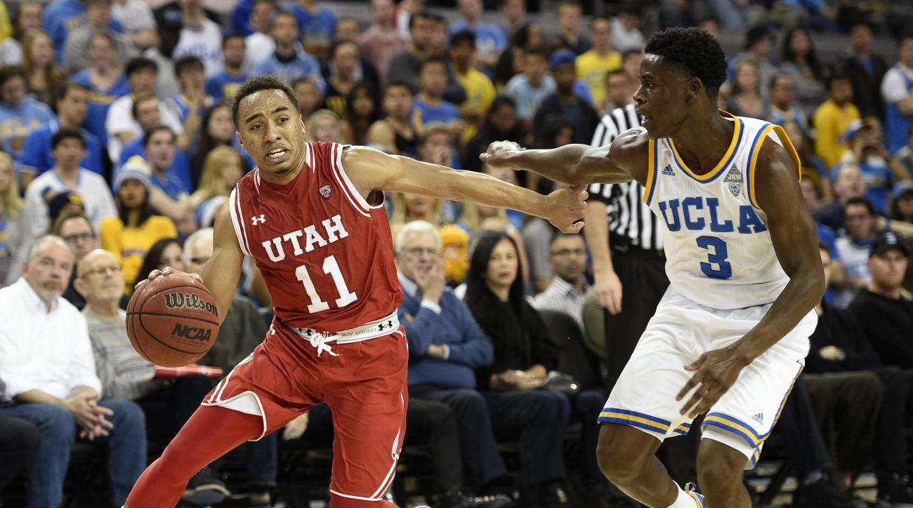 Utah guard Brandon Taylor, left, moves the ball as UCLA guard Aaron Holiday, right, defends during the first half of an NCAA basketball game, Thursday, Feb. 18, 2016, in Los Angeles. (AP Photo/Kelvin Kuo)