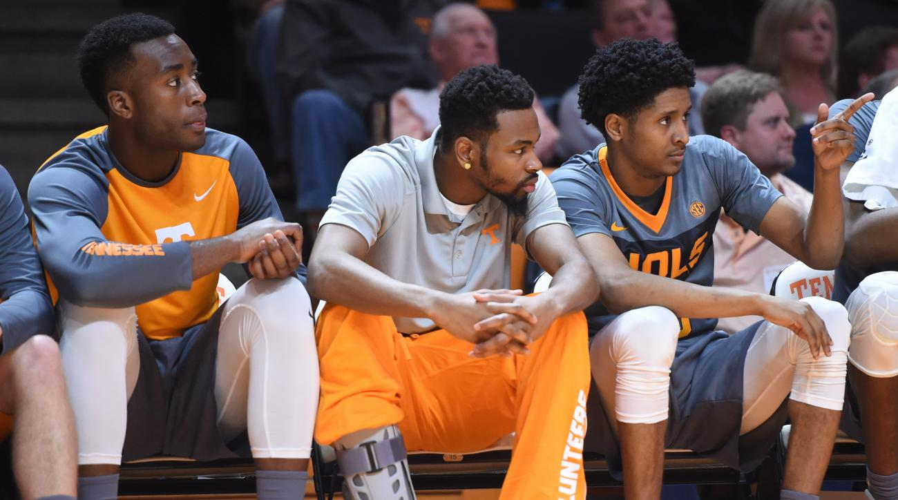 Tennessee guard Kevin Punter (0), center, sits on the bench with a leg brace with teammates Ray Kasongo (2) and Detrick Mostella (15), from left, during an NCAA college basketball game against LSU in Knoxville, Tenn., on Saturday, Feb. 20, 2016. Tennessee