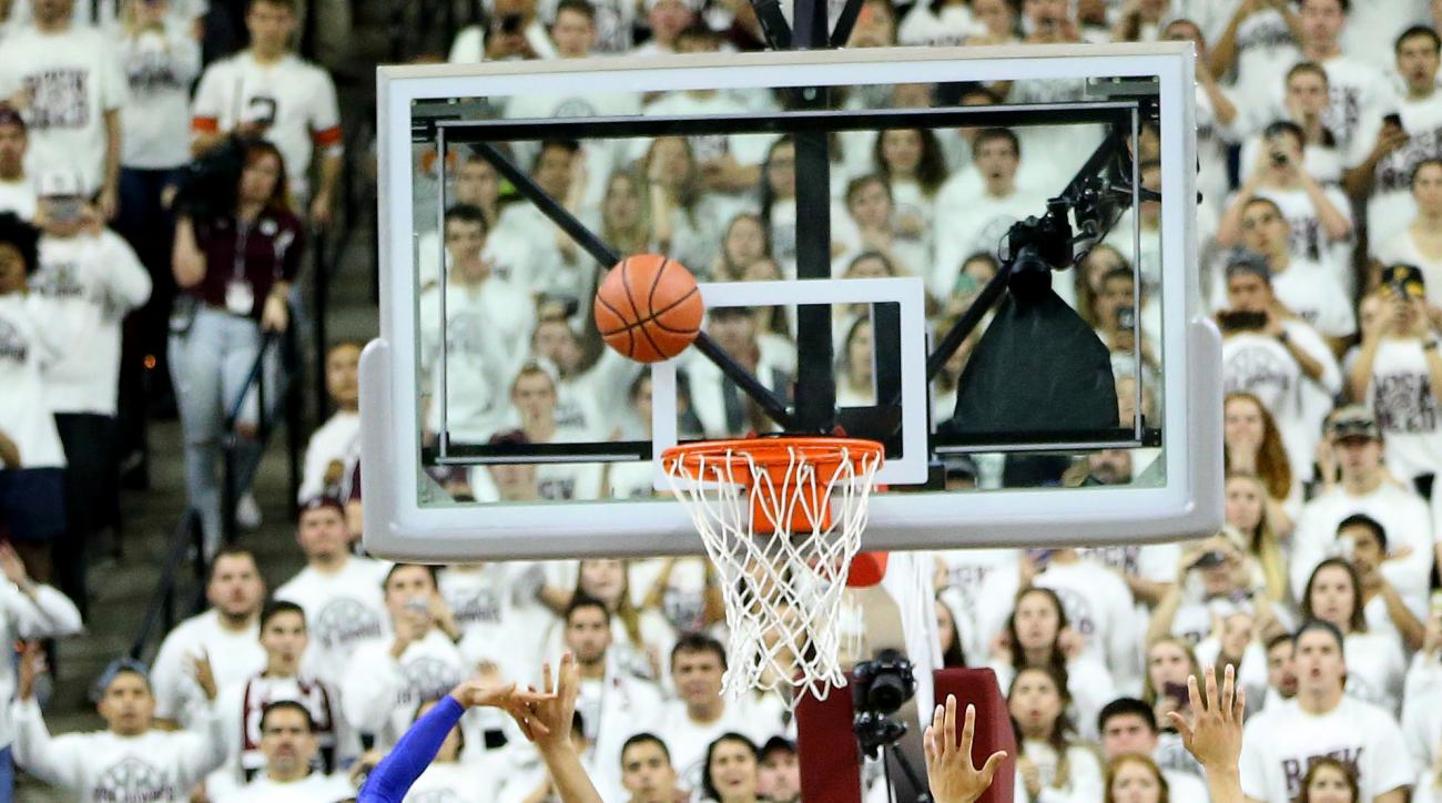 Texas A&M's Tyler Davis (34) makes a shot at the buzzer as Kentucky's Jamal Murray (23) defends during overtime of an NCAA college basketball game, Saturday, Feb. 20, 2016, in College Station, Texas. Texas A&M won 79-77. (AP Photo/Sam Craft)