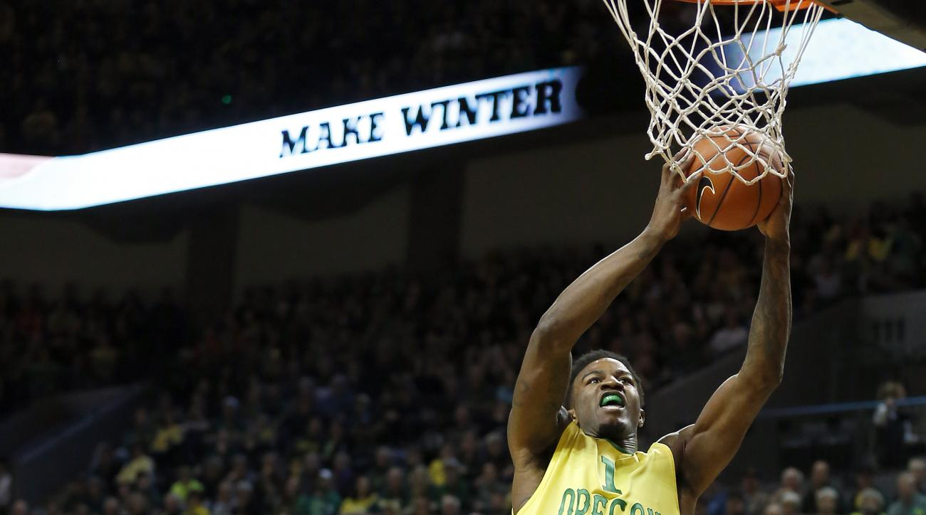 Oregon's Jordan Bell, right, jumps towards the basket in front of Oregon State's Gary Payton II, middle, and Cheikh N'diaye, left, during the first half of an NCAA college basketball game Saturday, Feb. 20, 2016, in Eugene, Ore. (AP Photo/Ryan Kang)