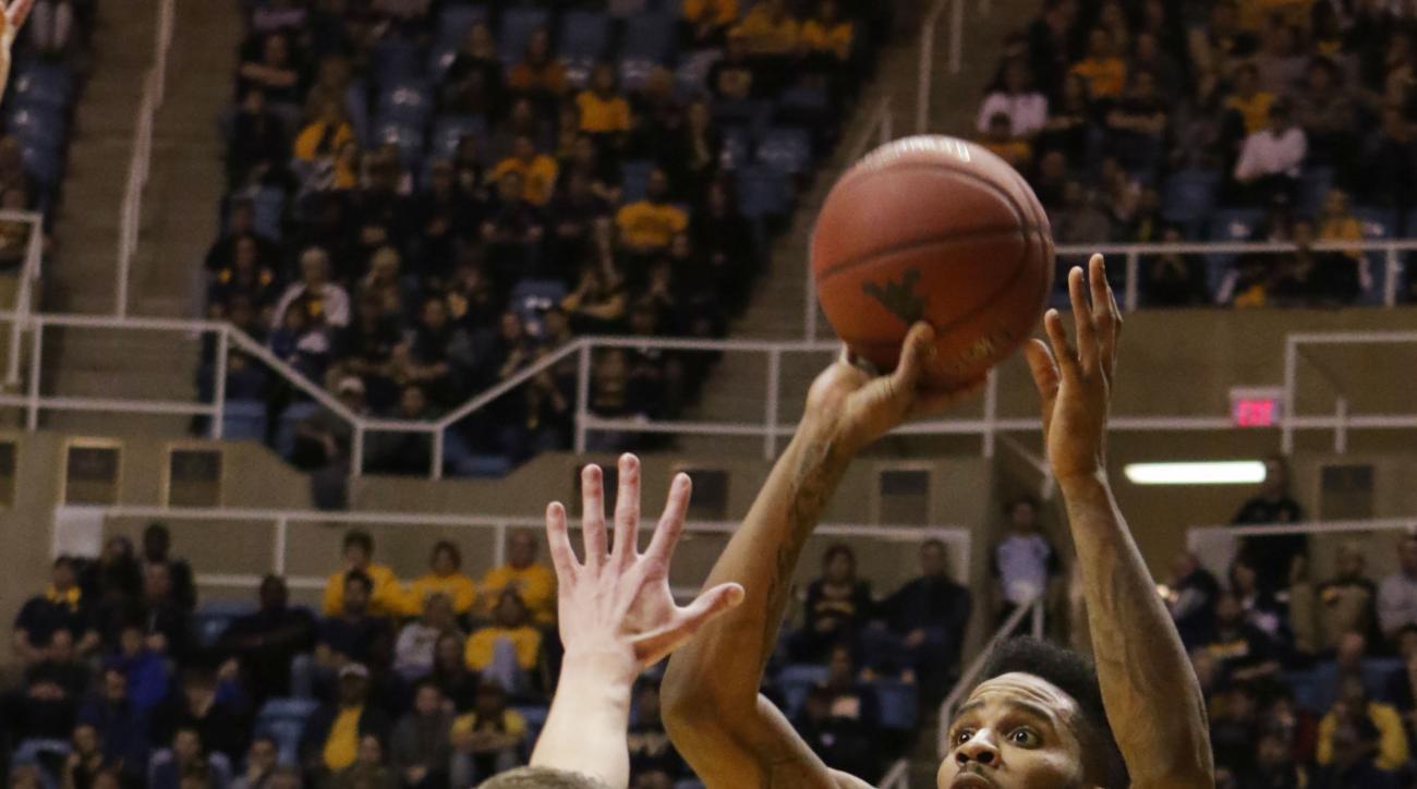 West Virginia guard Tarik Phillip (12) takes a shot over Iowa State guard Matt Thomas (21) during the second half of an NCAA college basketball game, Monday, Feb, 22, 2016, in Morgantown, W.Va. (AP Photo/Raymond Thompson)