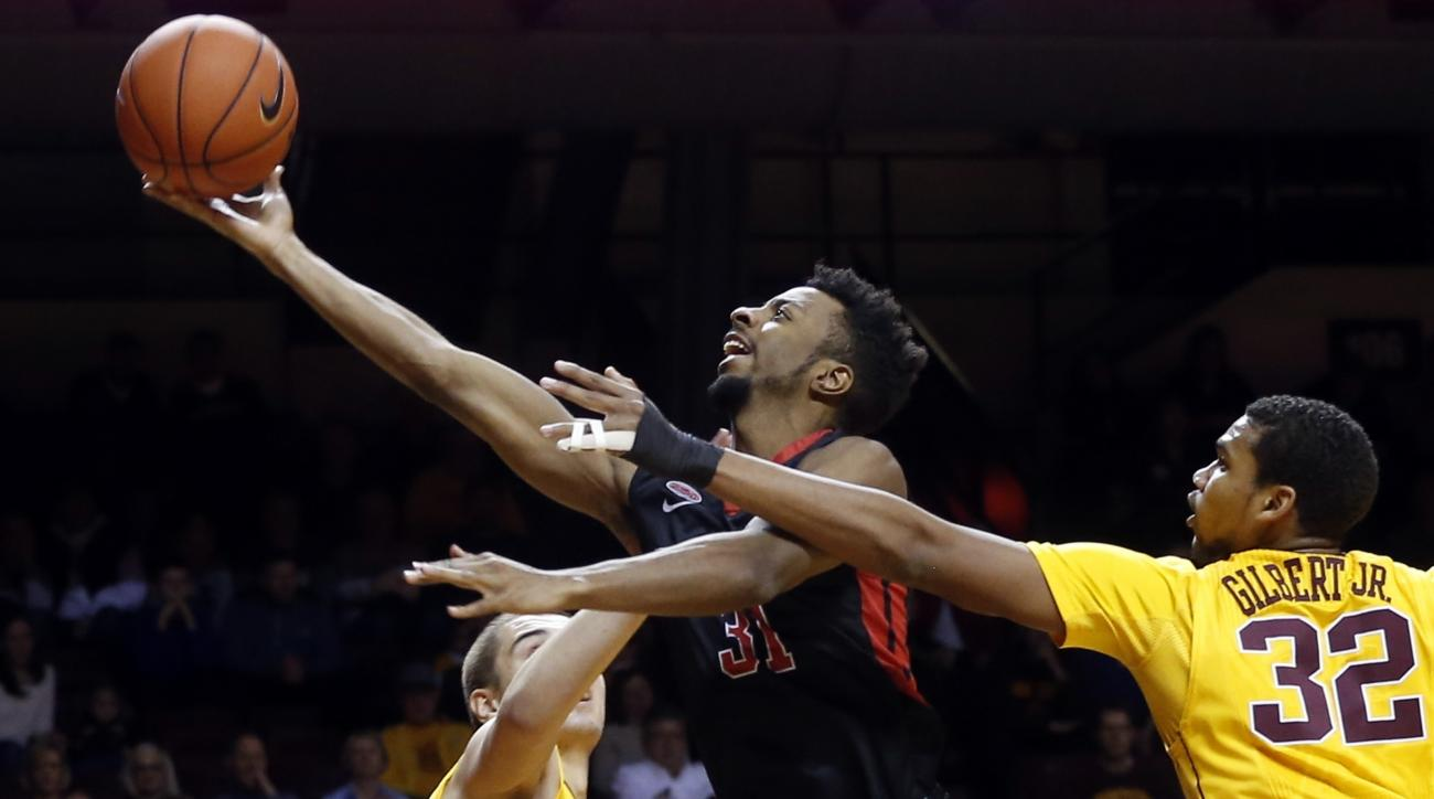 Rutgers' Omari Grier, center, lays up between Minnesota's Ahmad Gilbert Jr., right, and another defender during the first half of an NCAA college basketball game Tuesday, Feb. 23, 2016, in Minneapolis. (AP Photo/Jim Mone)