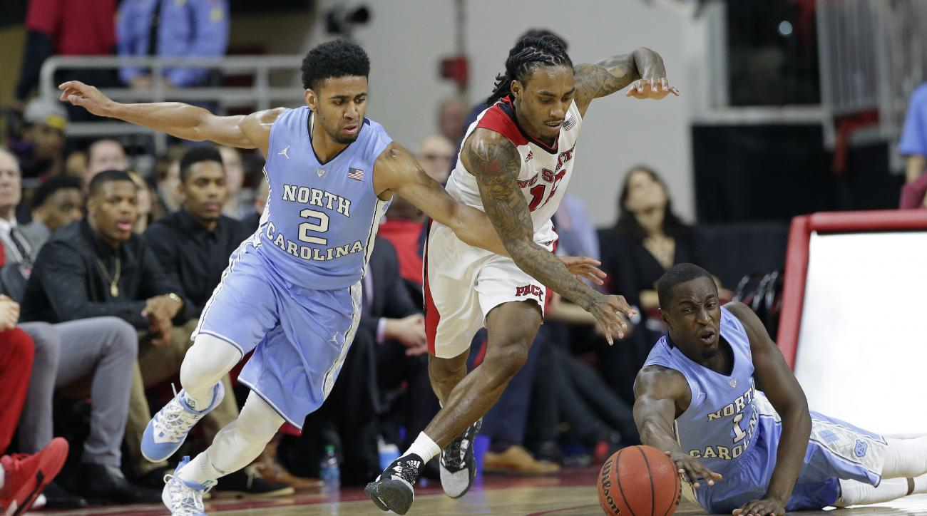 North Carolina's Joel Berry II (2) and Theo Pinson (1) chase the ball with North Carolina State's Anthony Barber, center, during the second half of an NCAA college basketball game in Raleigh, N.C., Wednesday, Feb. 24, 2016. North Carolina won 80-68. (AP P