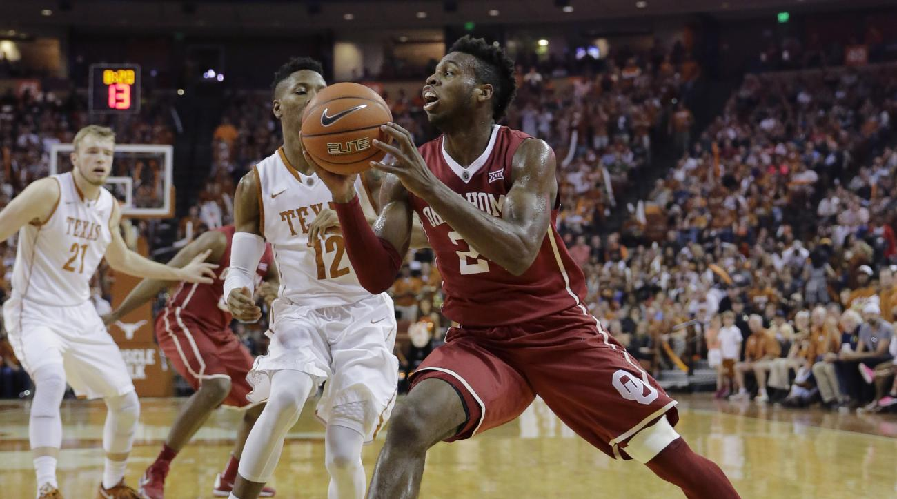 Oklahoma forward Khadeem Lattin (12) drives the ball around Texas guard Kerwin Roach Jr. (12) during the first half of an NCAA college basketball game, Saturday, Feb. 27, 2016, in Austin, Texas. (AP Photo/Eric Gay)