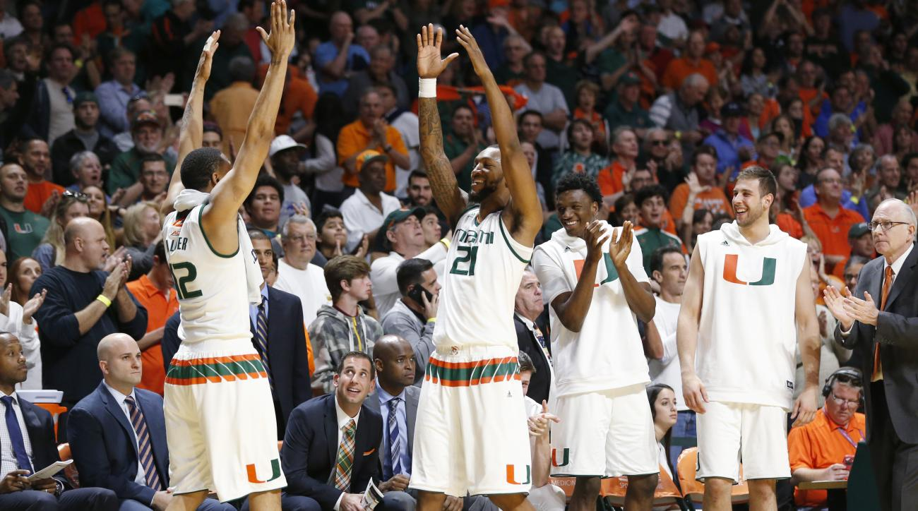Miami guard James Palmer (12) and forward Kamari Murphy (21) celebrate in the final seconds of the second half of an NCAA college basketball game against Louisville, Saturday, Feb. 27, 2016, in Coral Gables, Fla. Miami defeated Louisville 73-65. (AP Photo
