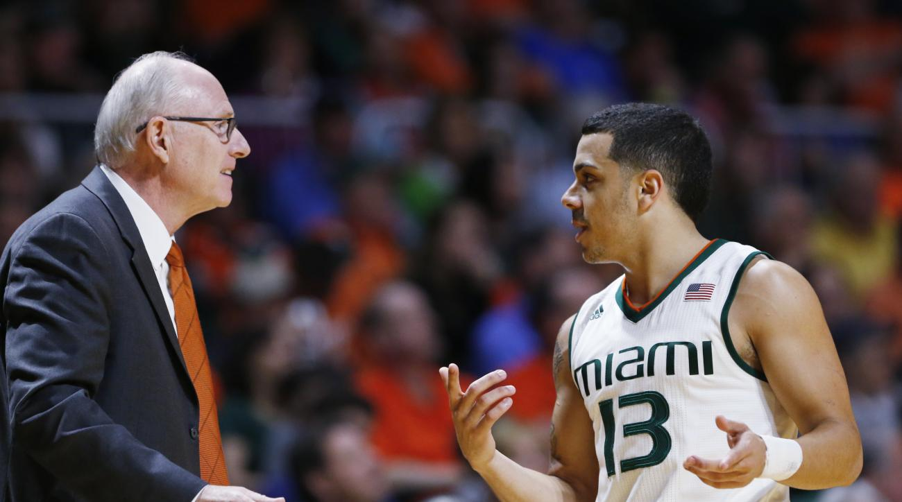 Miami head coach Jim Larranaga, left, talks with guard Angel Rodriguez (13) during the first half of an NCAA college basketball game against Louisville, Saturday, Feb. 27, 2016, in Coral Gables, Fla. Miami defeated Louisville 73-65. (AP Photo/Wilfredo Lee