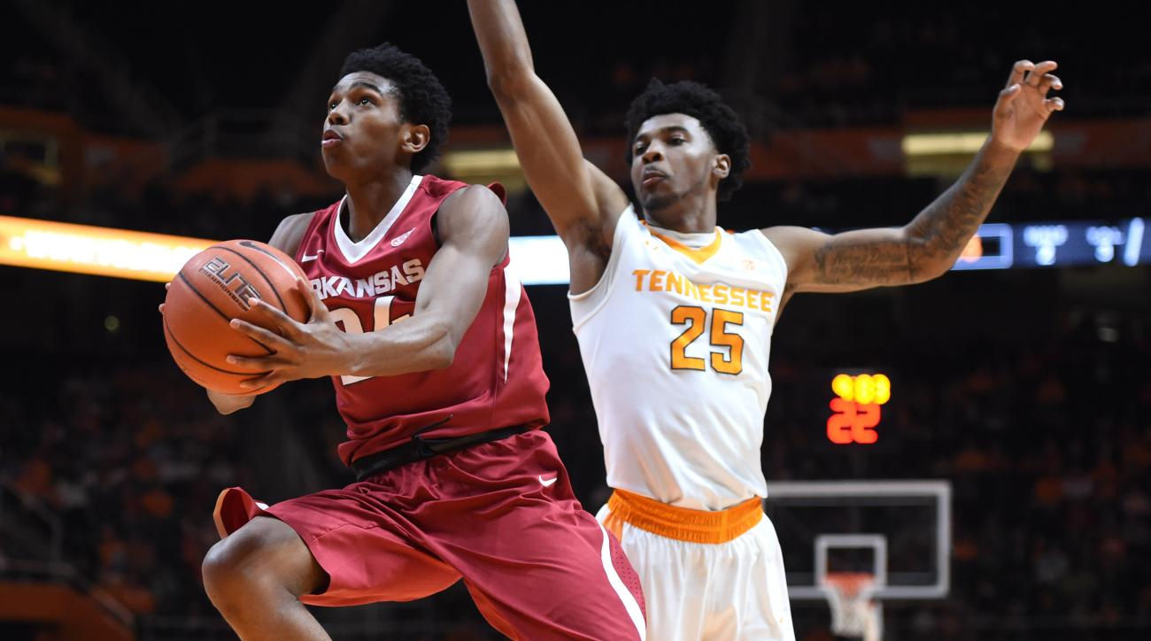 Arkansas guard Jimmy Whitt (24) leaps for a layup past Tennessee guard Shembari Phillips (25) during an NCAA college basketball game in Knoxville, Tenn., Saturday, Feb. 27, 2016. Arkansas won 75-65. (Adam Lau/Knoxville News Sentinel via AP)
