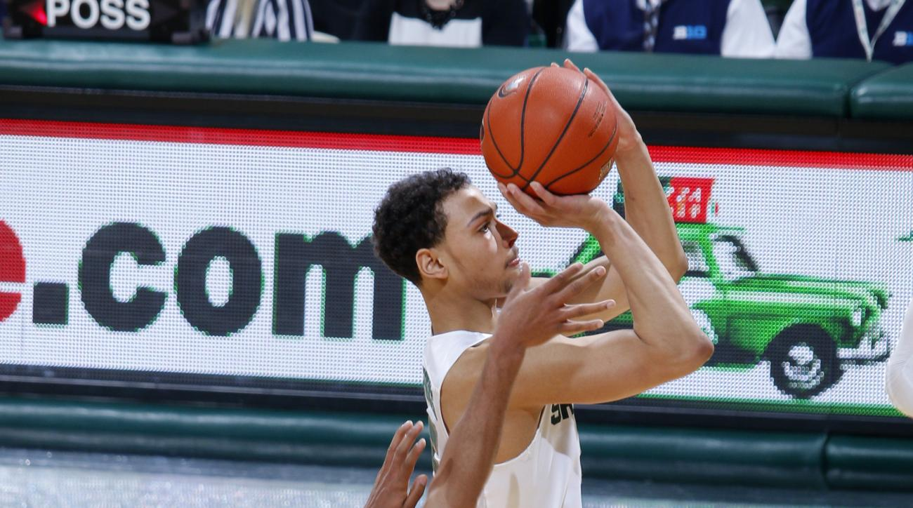 Michigan State's Bryn Forbes, right, shoots a three-pointer against Penn State's Shep Garner during the first half of an NCAA college basketball game, Sunday, Feb. 28, 2016, in East Lansing, Mich. (AP Photo/Al Goldis)
