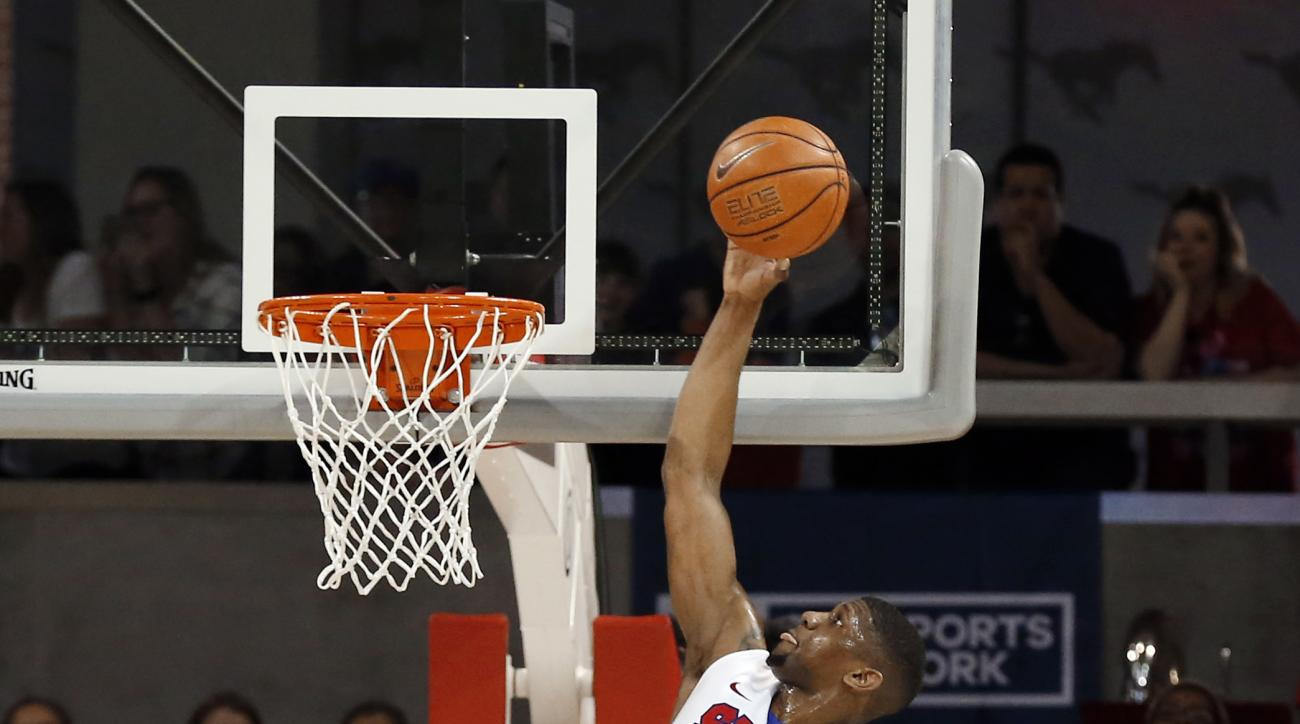 Tulane guard Louis Dabney, left, and Von Julien, right, watch as SMU forward Jordan Tolbert (23) goes up for a shot in the first half of an NCAA college basketball game, Sunday, Feb. 28, 2016, in Dallas. (AP Photo/Brad Loper)
