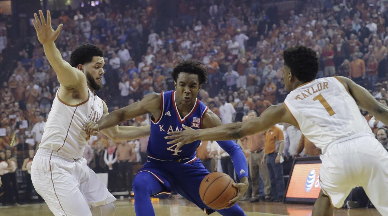 Kansas guard Devonte' Graham (4) drives between Texas guard Javan Felix (3) and guard Isaiah Taylor (1) during the first half of an NCAA college basketball game, Monday, Feb. 29, 2016, in Austin, Texas. (AP Photo/Eric Gay)