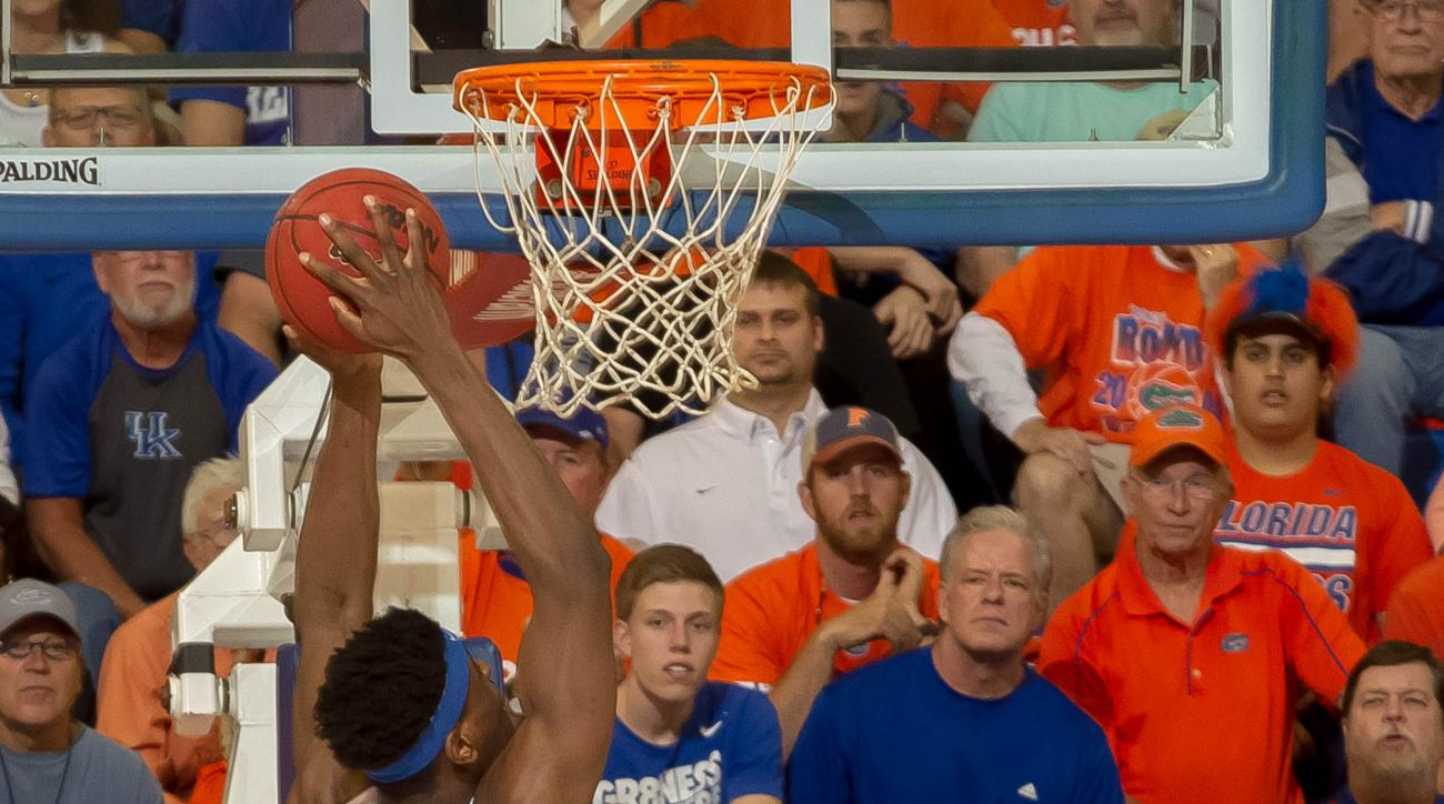 Florida center John Egbunu (15) dunks the ball as Kentucky forward Alex Poythress (22) looks on during the first half of an NCAA college basketball game in Gainesville, Fla., on Tuesday, March 1, 2016. (AP Photo/Ronald Irby)