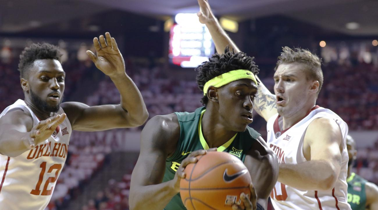 Oklahoma forwards Khadeem Lattin (12) and Ryan Spangler defend Baylor forward Johnathan Motley during the first half of an NCAA college basketball game in Norman, Okla., Tuesday, March 1, 2016. (AP Photo/Alonzo Adams)