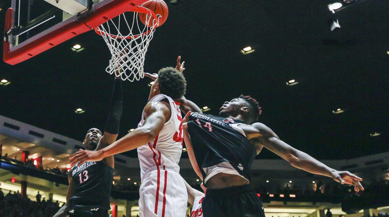 San Diego State's Winston Shepard (13), Zylan Cheatham (14) and New Mexico's Tim Williams, center, battle for a rebound during the first half of an NCAA basketball game, Tuesday, March 1, 2016, in Albuquerque, N.M. (AP Photo/Juan Labreche)
