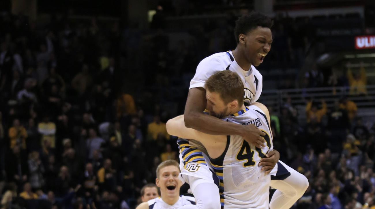 Marquette center Luke Fischer, center, is swarmed by teammates after making free throws in the final seconds of an NCAA college basketball game against Georgetown on Tuesday, March 1, 2016, in Milwaukee. Marquette defeated Georgetown 88-87. (AP Photo/Darr