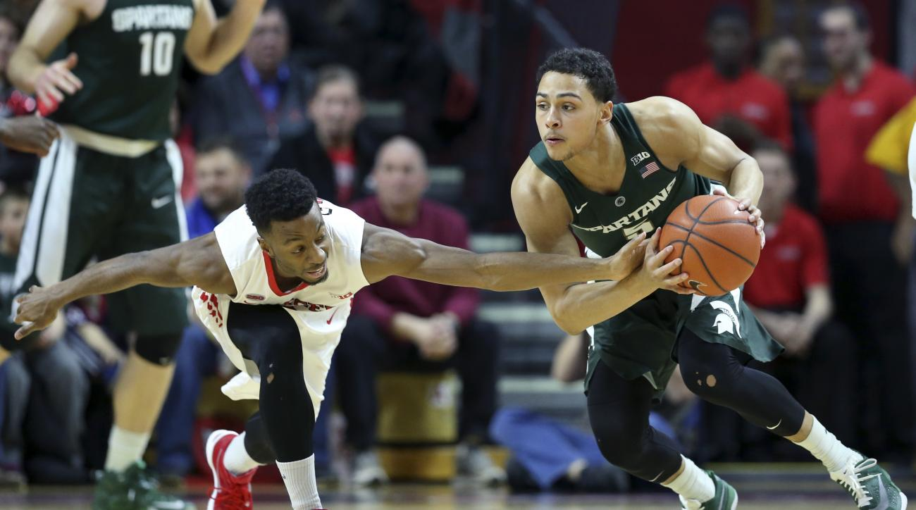 Rutgers guard Omari Grier, left, tries to make a steal as Michigan State guard Bryn Forbes tries to control the ball during the first half of an NCAA college basketball game Wednesday, March 2, 2016, in Piscataway, N.J. (AP Photo/Mel Evans)
