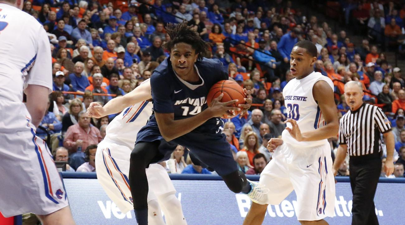 Nevada's Lindsey Drew (14) leaps with the ball between Boise State's Anthony Drmic, left rear, and Paris Austin (30) during the first half of an NCAA college basketball game in Boise, Idaho, Wednesday, March 2, 2016. (AP Photo/Otto Kitsinger)