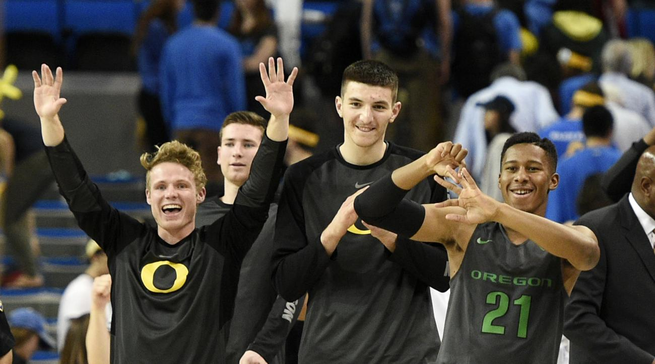 Oregon guard Max Heller, left, celebrates with forward Roman Sorkin, center, and guard Kendall Small, right, after an NCAA college basketball game against UCLA in Los Angeles, Wednesday, March 2, 2016. Oregon won 76-68. (AP Photo/Kelvin Kuo)