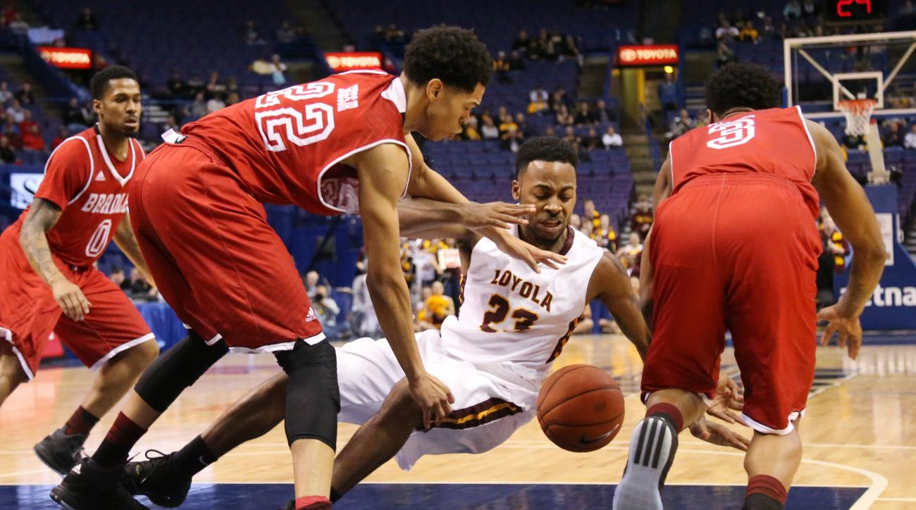 Loyola of Chicago guard Jeff White, center, loses possession of the ball as he drives against Bradley guards Ronnie Suggs, front left, and Antoine Pittman, right, during the first half of an NCAA college basketball game in the Missouri Valley Conference m