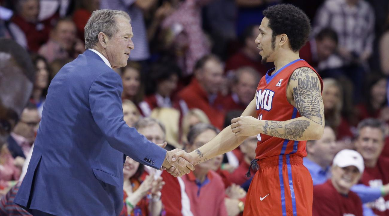 SMU guard Nic Moore, right, shakes hands with former President George W. Bush before SMU's NCAA college basketball game against Connecticut on Thursday, March 3, 2016, in Dallas. (AP Photo/LM Otero)
