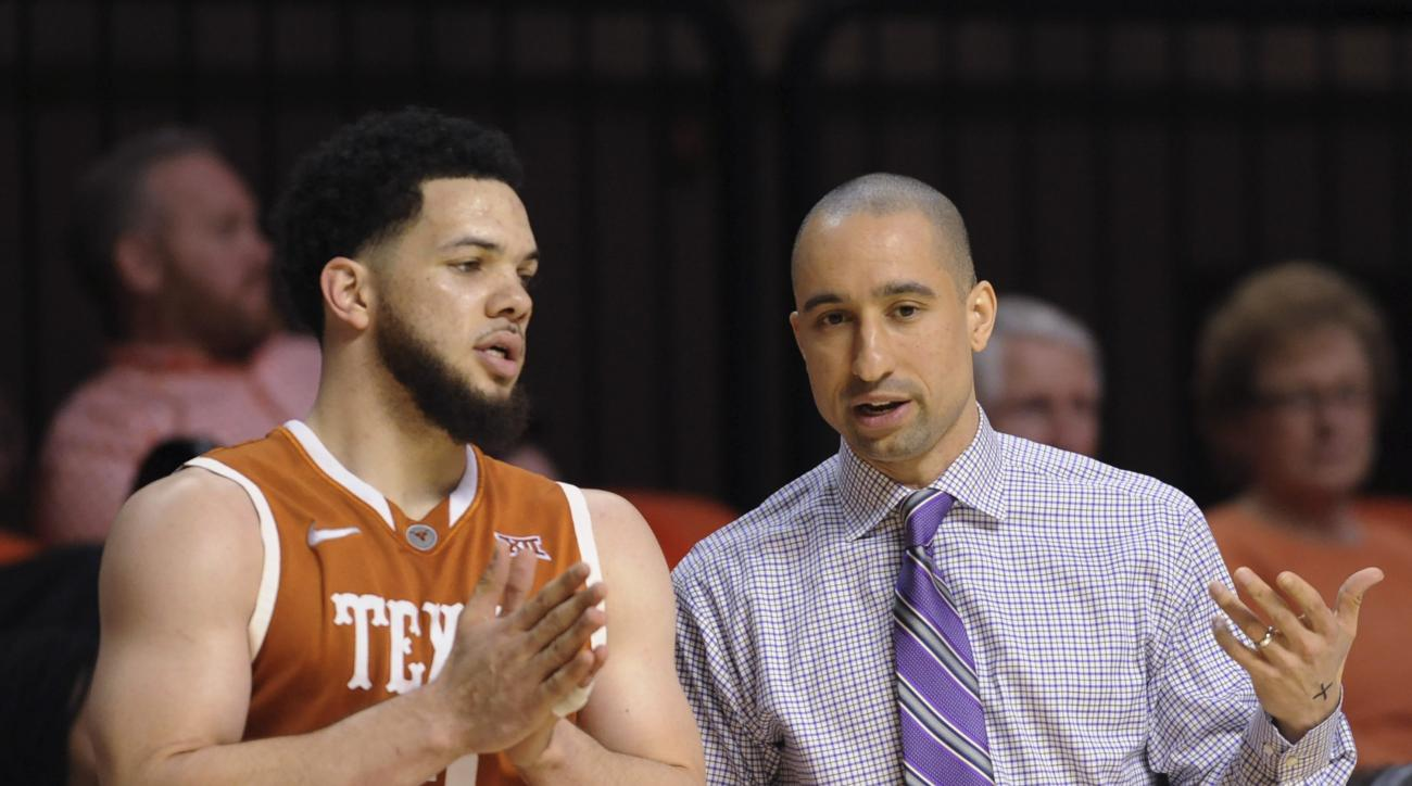 Texas guard Javan Felix, left, speaks with coach Shaka Smart prior to an inbounds play during the second half of an NCAA college basketball game against Oklahoma State in Stillwater, Okla., Friday, March. 4, 2016. Texas won 62-50. (AP Photo/Brody Schmidt)