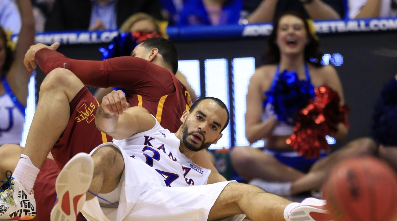 Kansas forward Perry Ellis (34) and Iowa State forward Abdel Nader, back, hit the floor during the first half of an NCAA college basketball game in Lawrence, Kan., Saturday, March 5, 2016. Ellis passed to a teammate from the floor. (AP Photo/Orlin Wagner)
