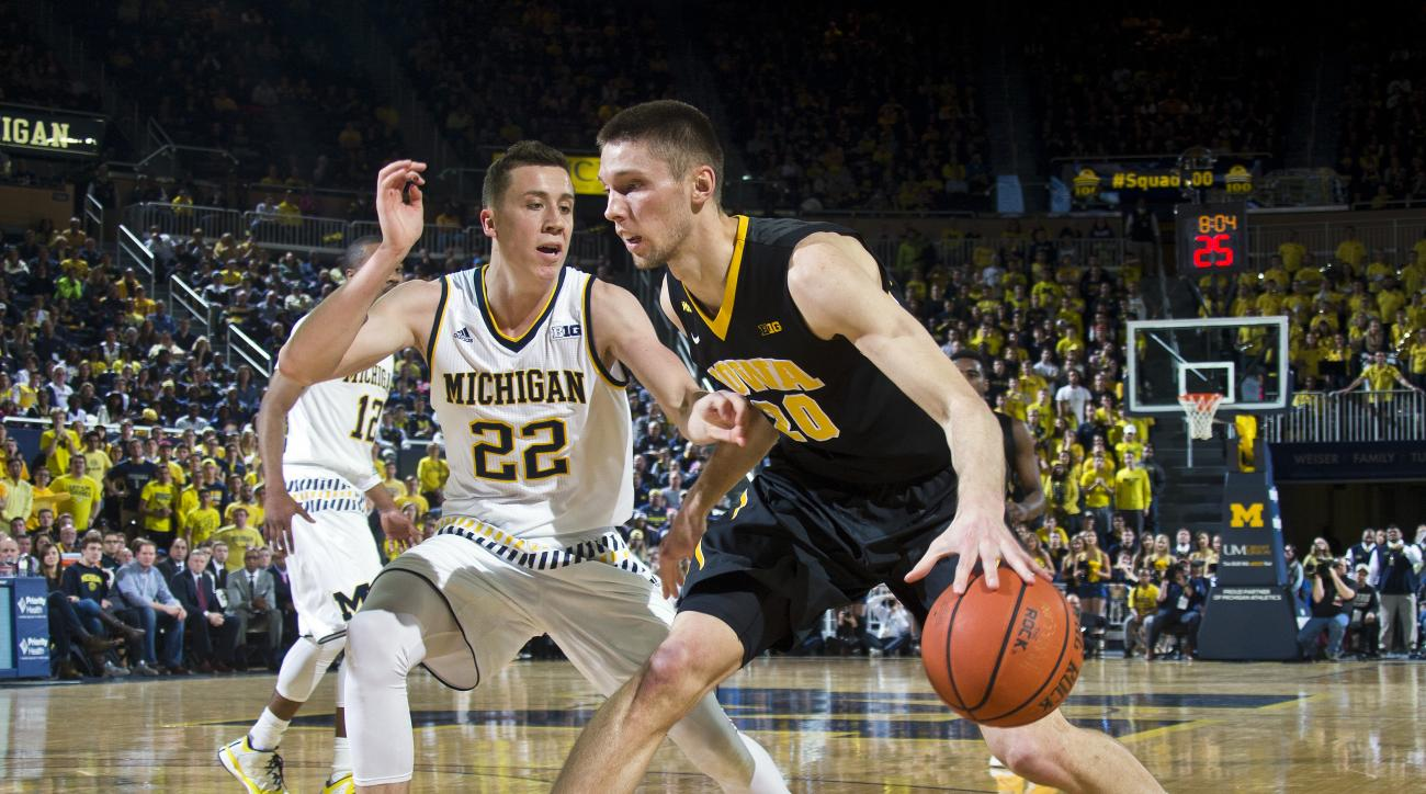 Michigan guard Duncan Robinson (22) defends Iowa forward Jarrod Uthoff (20) in the first half of an NCAA college basketball game at Crisler Center in Ann Arbor, Mich., Saturday, March 5, 2016. (AP Photo/Tony Ding)