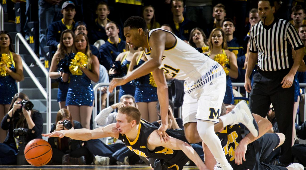 Iowa guard Mike Gesell, bottom, reaches for the loose ball, competing with Michigan guard Zak Irvin, top, in the first half of an NCAA college basketball game at Crisler Center in Ann Arbor, Mich., Saturday, March 5, 2016. (AP Photo/Tony Ding)