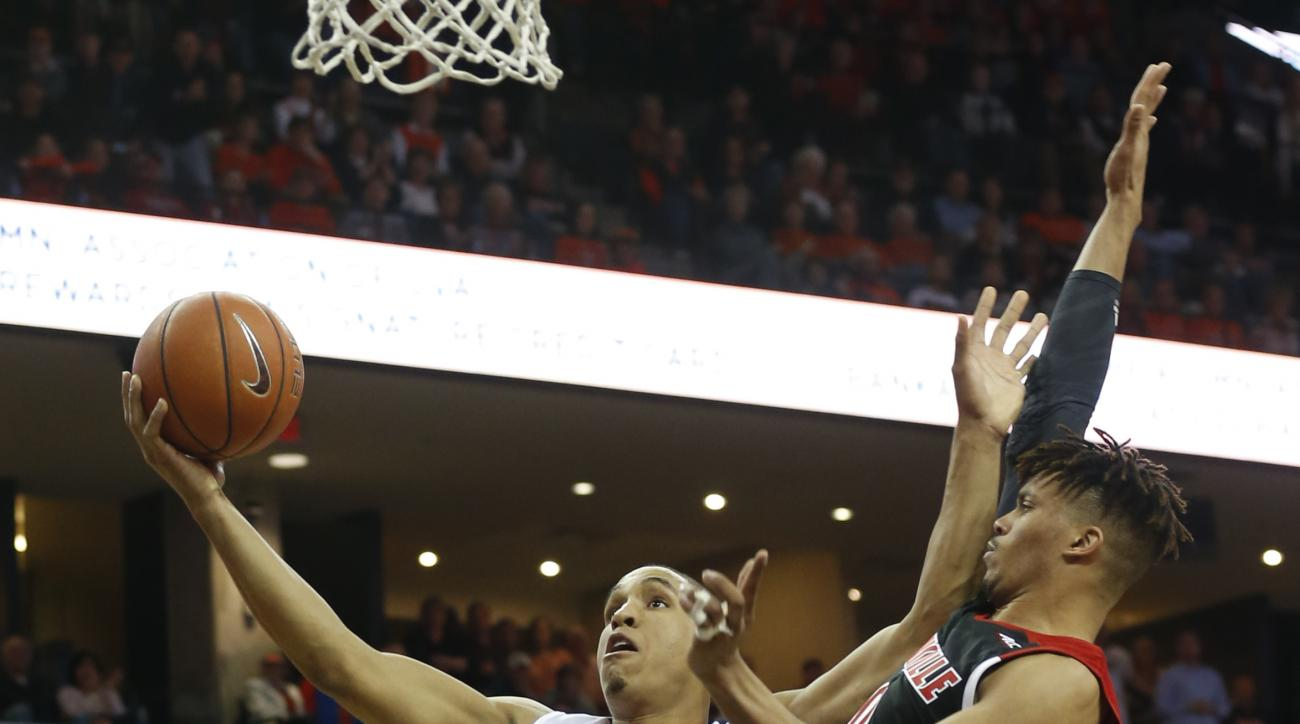 Virginia guard Malcolm Brogdon (15) fends off Louisville guard Damion Lee (0) during the first half of an NCAA college basketball game in Charlottesville, Va., Saturday, March 5, 2016. (AP Photo/Steve Helber)