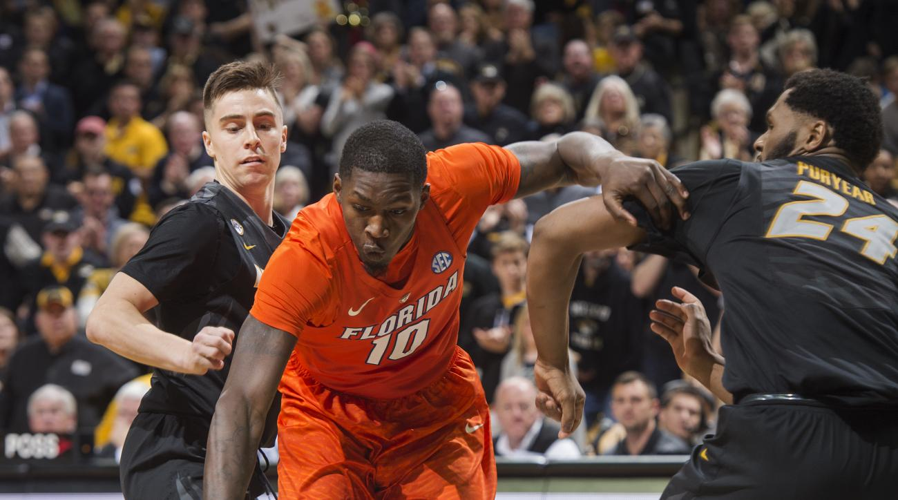 Florida's Dorian Finney-Smith, center, drives between Missouri's Kevin Puryear, right, and Jimmy Barton during the second half of an NCAA college basketball game Saturday, March 5, 2016, in Columbia, Mo. Florida won the game 82-72. (AP Photo/L.G. Patterso